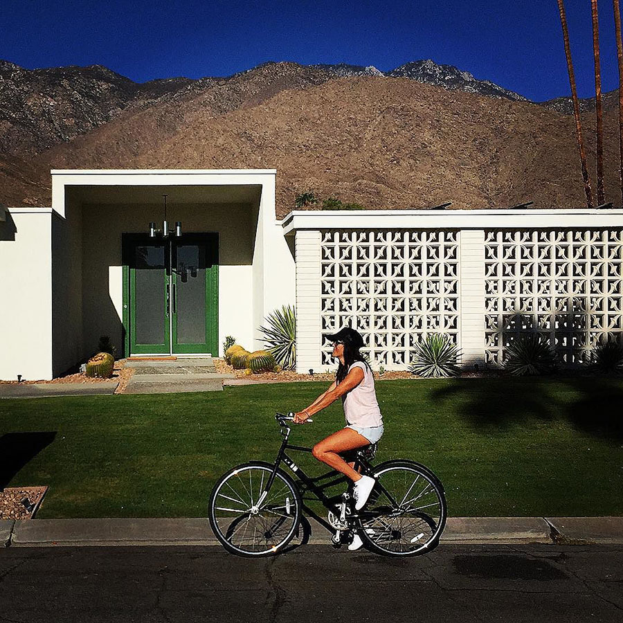 Woman on bike in front of home